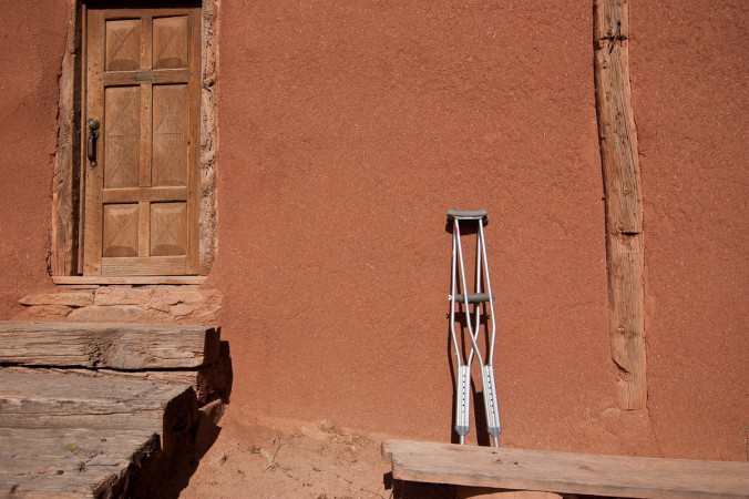 Crutches leaning against a clay wall